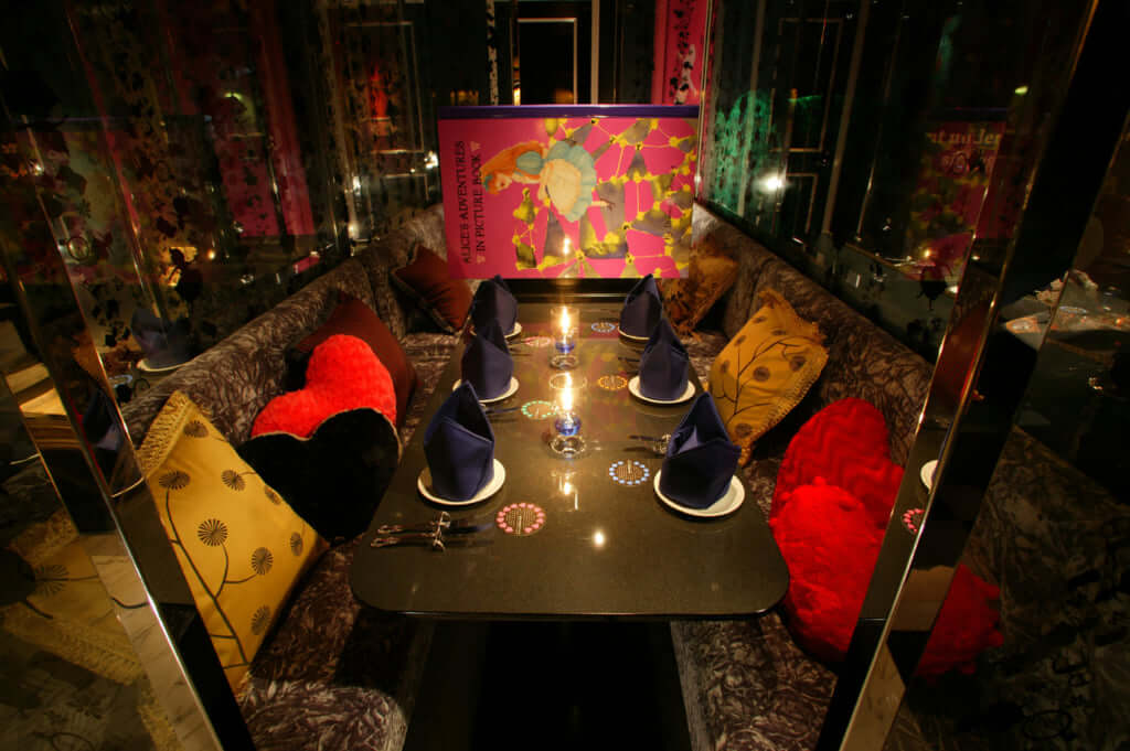 「出会い鏡の森」アリスのシルエットが描かれたガラスの壁に囲われた半個室タイプの席。